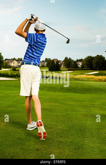 Rear view of teenage boy (16-17) playing golf - Stock Image