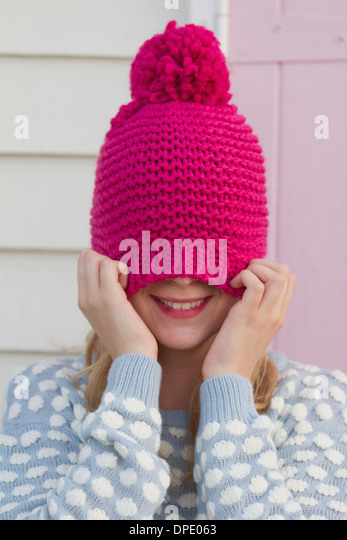 Portrait of young woman hiding under wooly hat - Stock Image