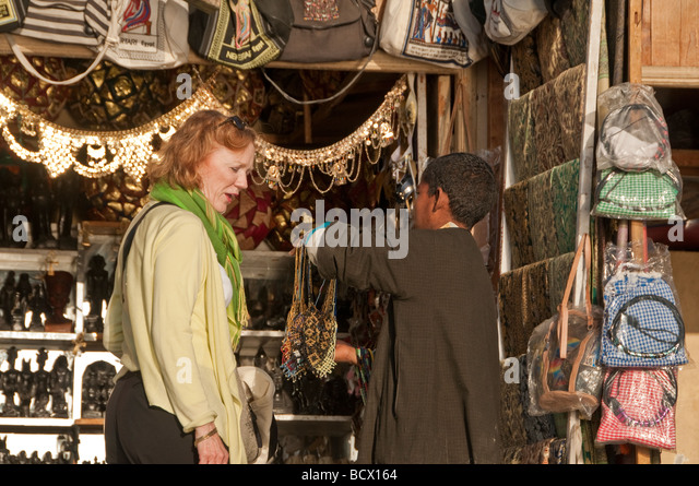 Egypt Kom Ombo village woman tourist red hair looking at souvenirs - Stock Image
