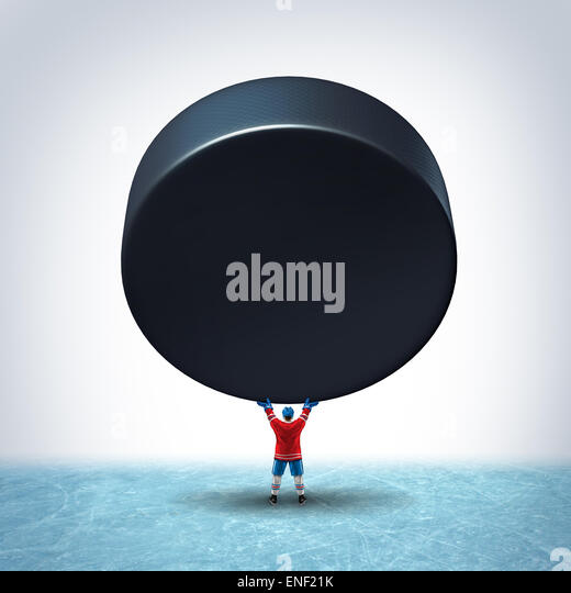 Hockey ice champion concept as a player in uniform holding up a giant puck with blank copy space on a rink as a - Stock-Bilder