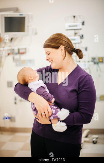 Mother standing in hospital ward holding baby son (6-11 months) - Stock Image