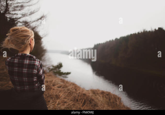 young woman standing on hill top admiring the beautiful view - Stock Image