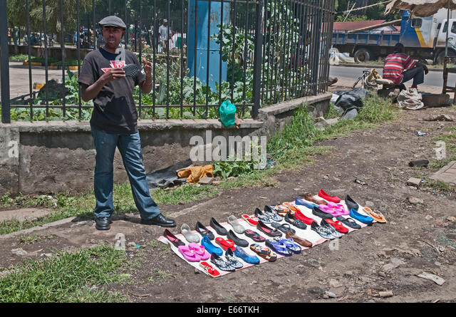 Man trying to sell shoes footware flip flops at side of road with shoes displayed on piece of cloth - Stock Image
