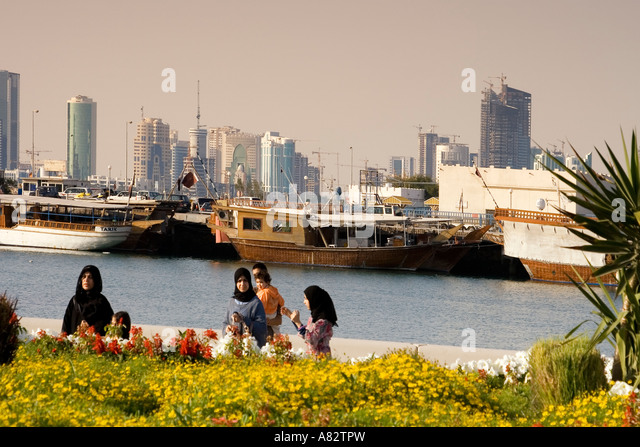 Qatar Doha bay skyline promenade veiled arabian women - Stock Image