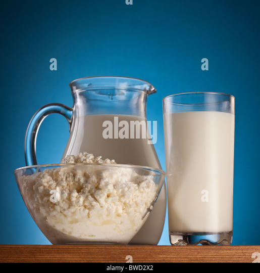 Milk and cottage cheese. On a blue background. - Stock Image