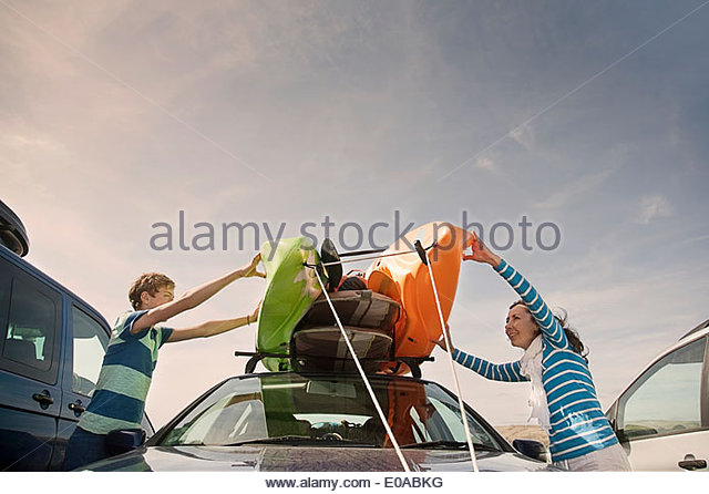 Mother and son stacking kayaks on top of car - Stock-Bilder