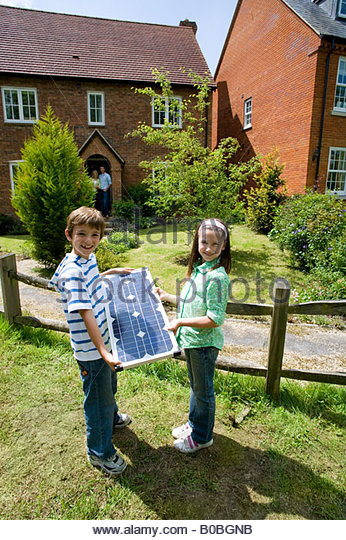 Brother and sister  with solar panel by house, portrait - Stock Image