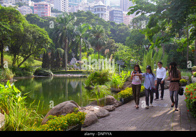 China Hong Kong Island Central Hong Kong Park landscape trees pond Asian woman friends city skyline - Stock Image
