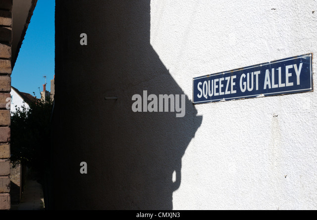 The street name sign for Squeeze Gut Alley in Whitstable, Kent. - Stock Image