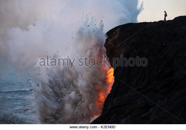 An unauthorized hiker in a restricted zone venturing out onto an unstable sea cliff over a lava tube where hot lava - Stock Image