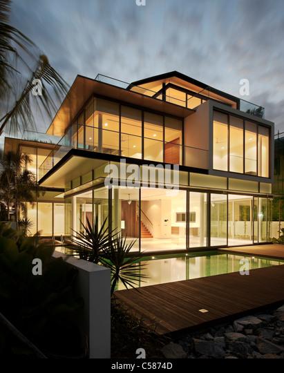 Modern glass house at dusk. - Stock Image