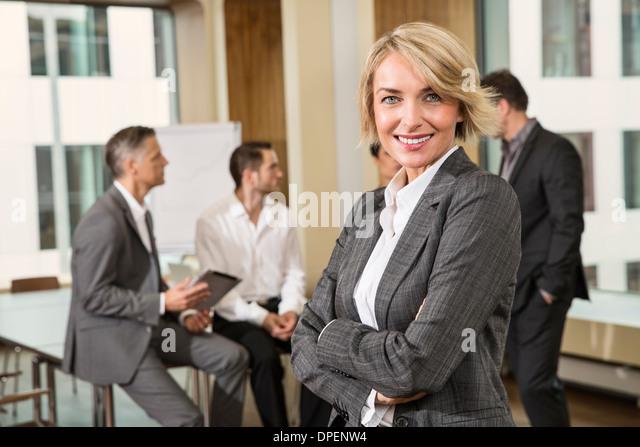 Businesswoman standing in front of colleagues - Stock-Bilder