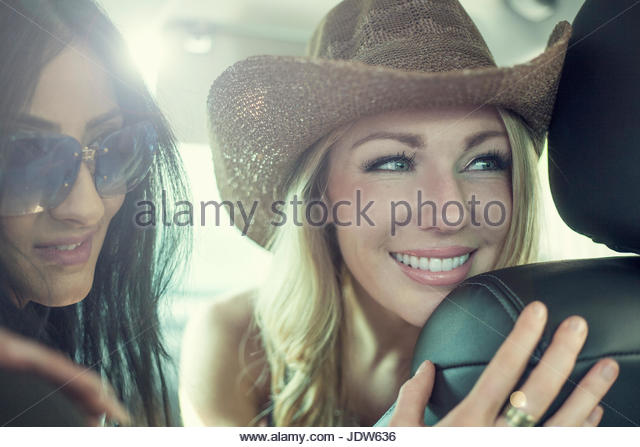 Two young women looking through car seats in car - Stock-Bilder