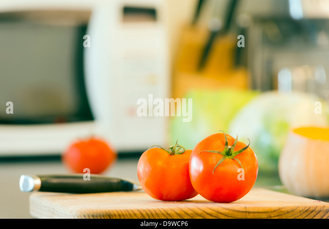 Preparing fresh food on the kitchen bench, with tomatoes, pumpkin and other vegetables in the background - Stock Image