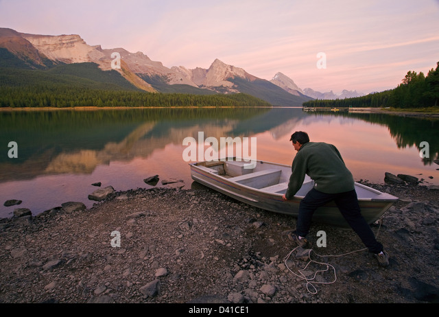 Middle age male pulling up row boat on shore at Maligne Lake, Jasper National Park, Alberta, Canada. - Stock Image