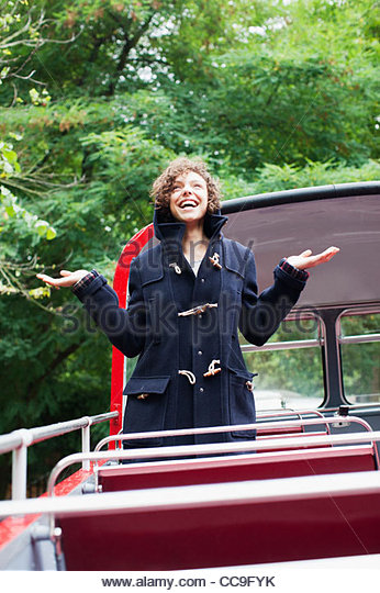 Exuberant woman standing with arms outstretched on double decker bus - Stock Image