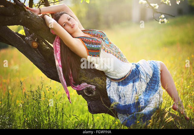 Beautiful romantic hippie posing in spring meadow. Gypsy dress - Stock Image