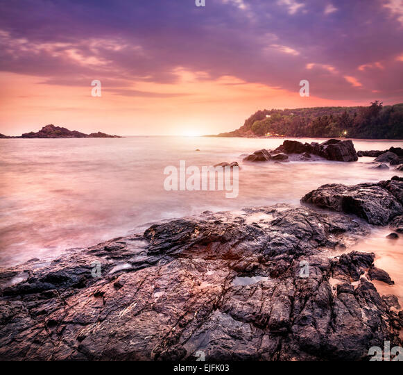 Sea with rocks at violet sunset sky in Om beach, Gokarna, Karnataka, India - Stock Image