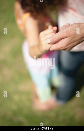 Mother and daughter holding hands, cropped - Stock Image