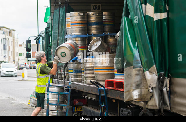 Delivering barrels of beer to a pub in the UK. - Stock Image