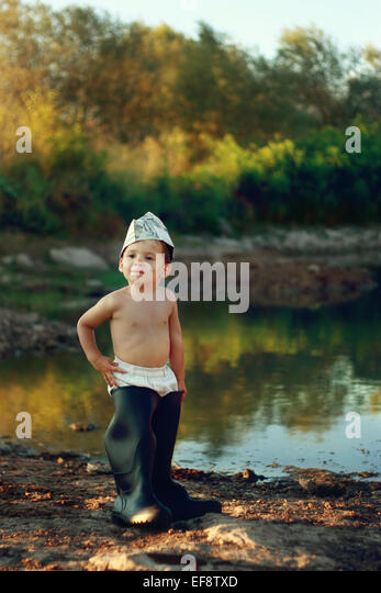 Boy (18-23 months) wearing huge rubber boots and paper hat standing by pond - Stock Image