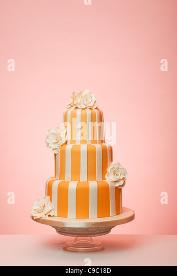 Orange striped wedding cake with peach background - Stock Image