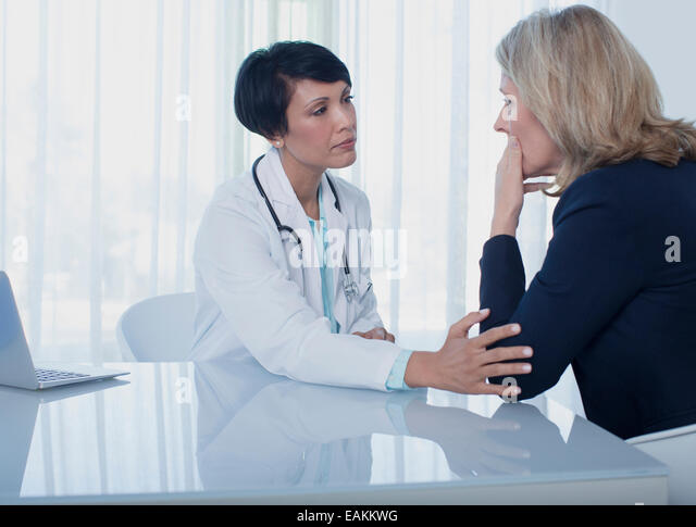 Female doctor consoling sad woman at desk in office - Stock Image