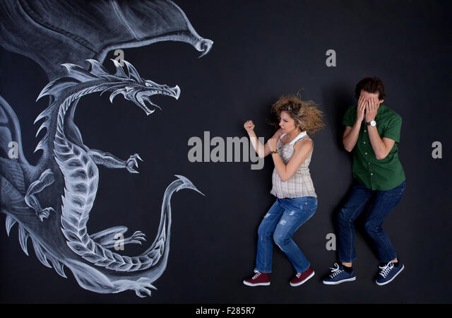 Young pregnant woman protecting his man against a drawing dragon. - Stock Image