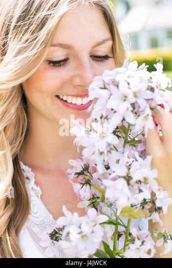 MODEL RELEASED. Young woman smelling white flowers. - Stock-Bilder