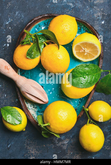 Freshly picked lemons with leaves in bright blue ceramic plate - Stock Image