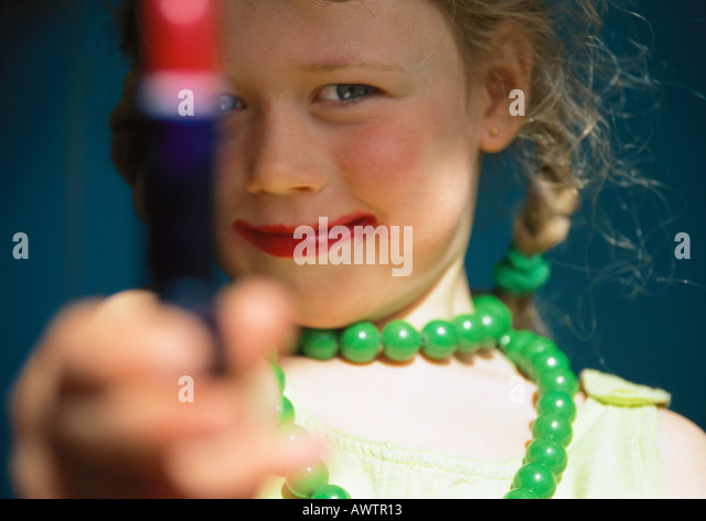 Little girl playing dress-up, holding out tube of lipstick - Stock Image