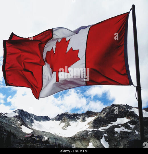 Canada, Whister, Flag of Canada waving over mountains - Stock Image