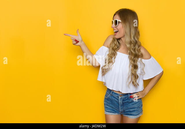 Ecstatic blond young woman in jeans shorts, white shirt and sunglasses holding hand on hip, looking away and pointing, - Stock Image