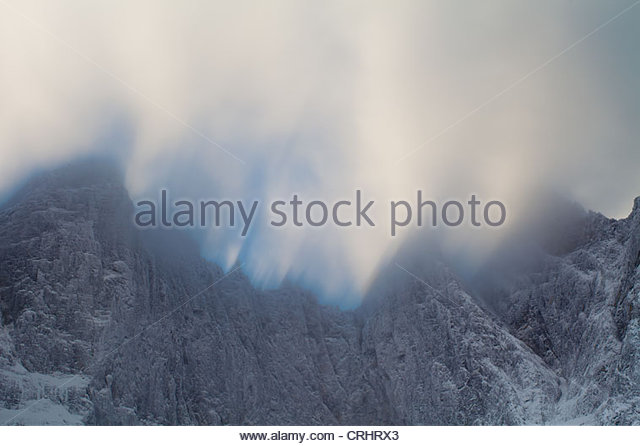 High winds and drifting clouds above the 3000 feet vertical Troll wall in the Romsdalen valley, Møre og Romsdal, - Stock Image