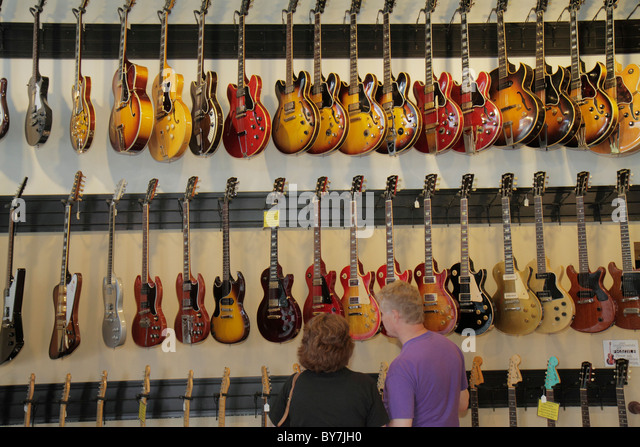 Nashville Tennessee Music City USA downtown Lower Broadway Gruhn Guitars business musical instruments display man - Stock Image