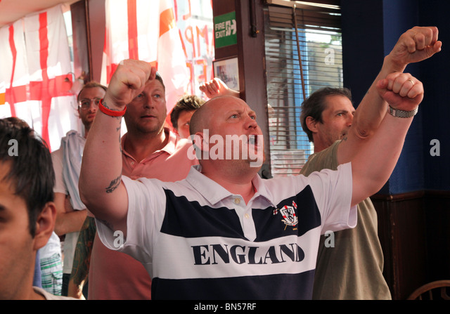 England football fans watching the 2010 World Cup game against Germany in a London pub - Stock Image