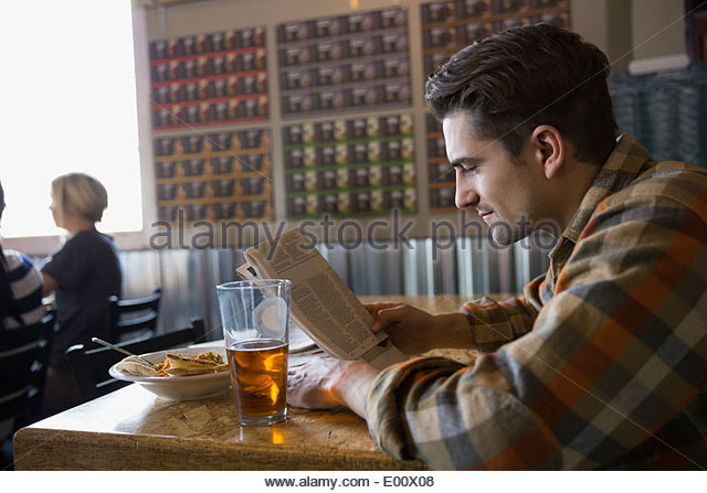 Man reading newspaper and enjoying lunch at brewery - Stock Image