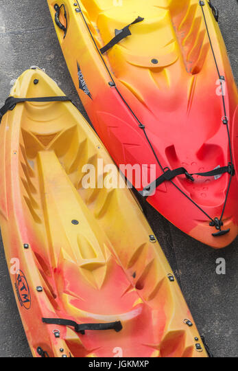 A couple of brightly coloured sea kayaks ready 'for hire' on the quayside at Newquay, Cornwall. - Stock Image
