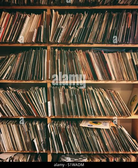 45 rpm records on shelves at a record store - Stock Image