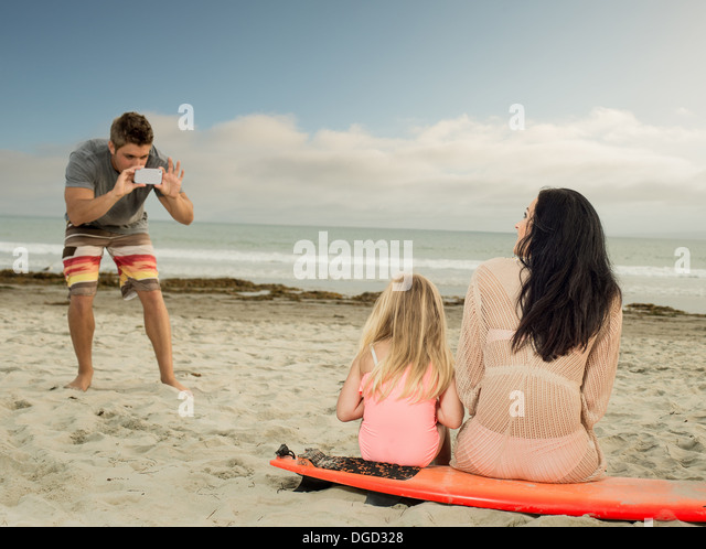 Man photographing family as the sit on a surfboard - Stock-Bilder