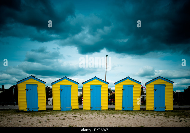 Yellow and Blue beach huts under a moody sky on Littlehampton beach, West Sussex - Stock Image