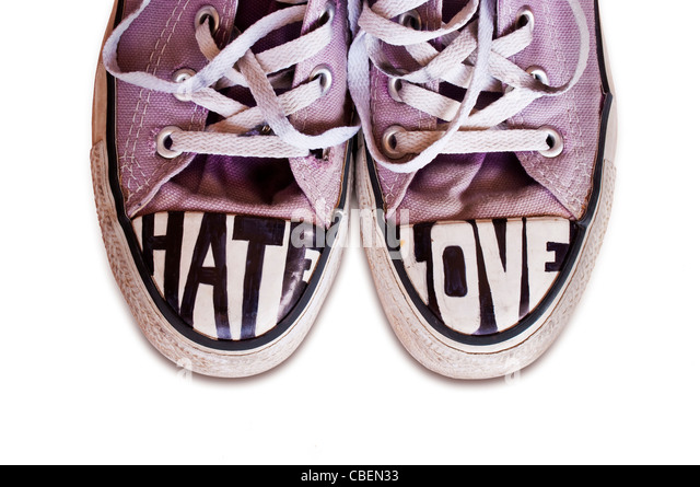 Teenagers converse shoes customized with the words Hate and Love on white background - Stock Image