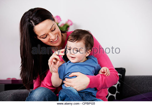 A mother and her baby son listening on a mobile phone - Stock-Bilder