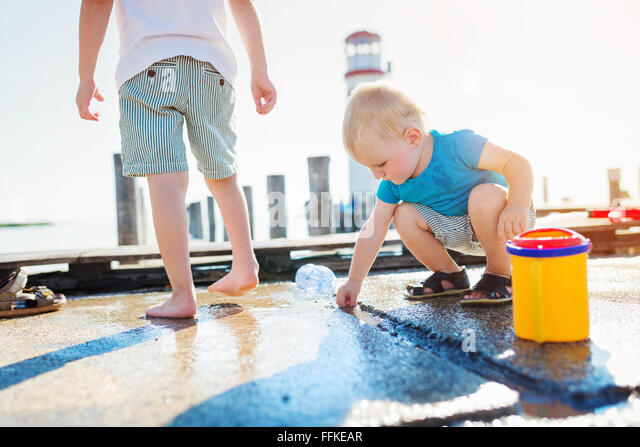 Two boys playing on the pier, lighthouse, sunny summer - Stock Image