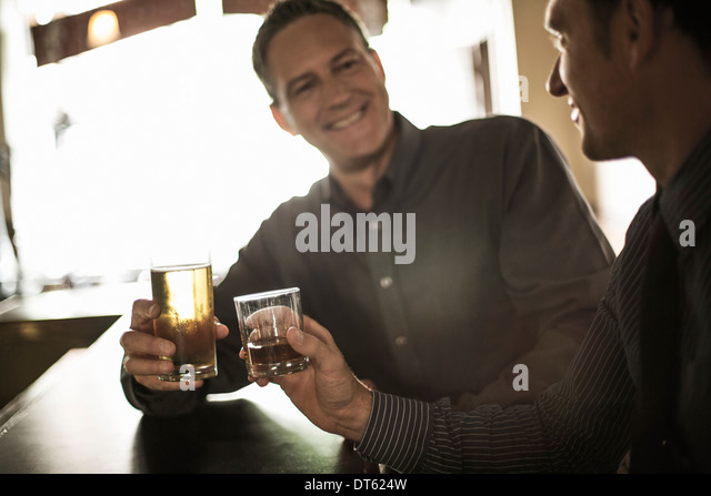Two businessmen toasting drinks at the bar - Stock Image