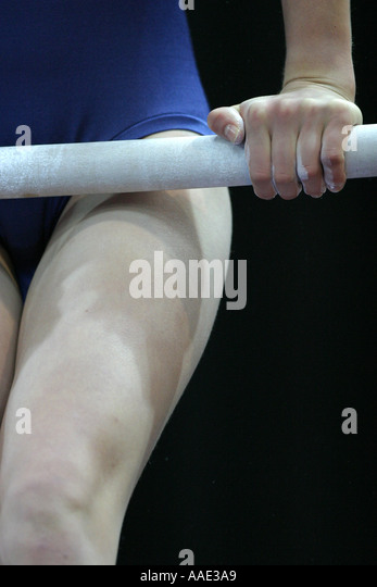Young female gymnast competing on the uneven bars - Stock Image