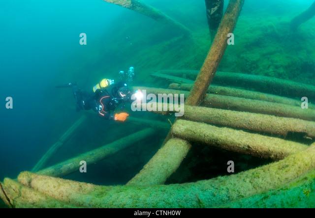 Diver surveys the destroyed wooden mooring, lake Baikal, Siberia, Russia, Eurasia - Stock Image