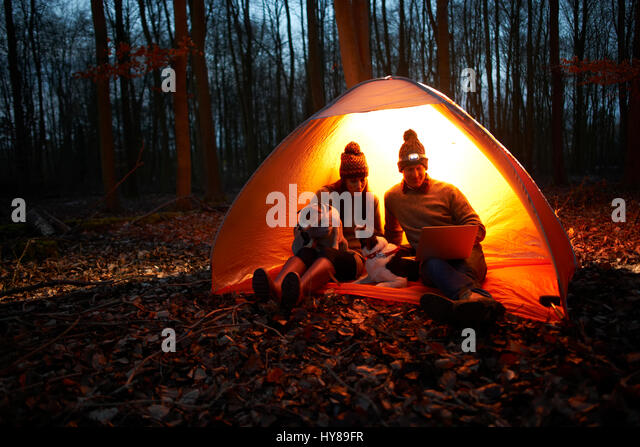 A couple sit in a tent at night with their dogs and look at their laptop - Stock Image