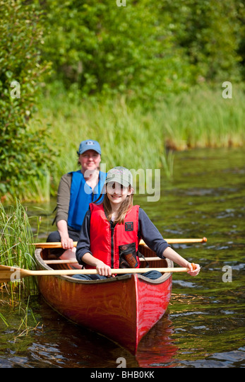 Mother and daughter paddling a canoe together on Byers Lake, Denali State Park, Southcentral Alaska, Summer - Stock Image