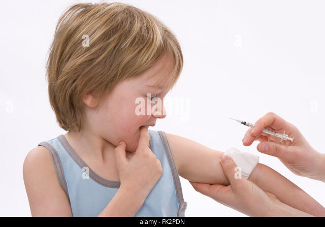Little boy is looking scared when he gets a vaccination on white background - Stock Image